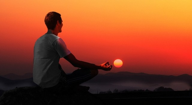guy.meditating.sunset